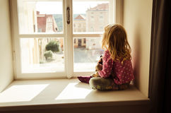 Girl looking over window. Little blond girl sitting and looking over window Stock Photography