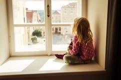 Girl looking over window Stock Photography