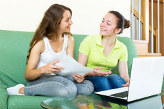 Girl looking papers with laptop Royalty Free Stock Images