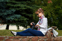 Girl is looking at photos in camera Stock Images