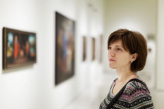 Girl looking pictures. In  museum Stock Photography