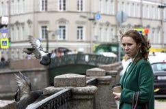 1 girl looks at pigeons, girl on city street, Saint Petersburg stock photo