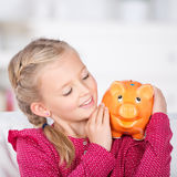 Girl looking at piggy bank smiling Royalty Free Stock Image