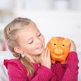 Girl looking at piggy bank smiling Royalty Free Stock Image
