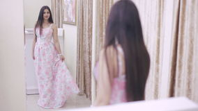 Girl looking for a prom dress. Girl trying on a dress in front of a mirror in a store stock video