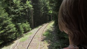 Girl looking at the railway from the last wagon in the forest - Georgia.  stock footage