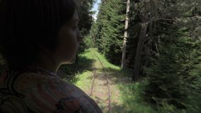 Girl looking at the railway from the last wagon in the forest - Georgia.  stock video footage