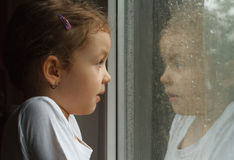Girl looking at raindrops on the window Stock Photo