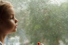 Girl looking at raindrops on the window Stock Photography