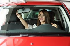 Girl is looking in the rearview mirrow. royalty free stock photography