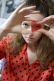 Girl looking through red glass Stock Images