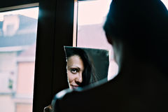 Girl looking at reflection in a mirror Stock Photo