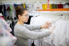 Girl looking for the right size t-shirt in a row of clothes