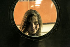 Girl looking through a round window Royalty Free Stock Photos