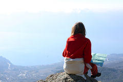 Girl looking at the sea. Girl hiker sitting on a rock and looking at the sea Stock Photo