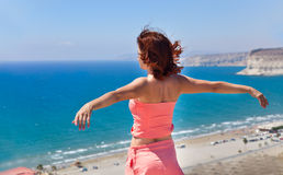 Girl is looking at sea. Girl is standing on rock and looking at sea. Her hands are raised up Royalty Free Stock Images