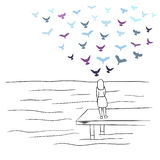A girl looking at sea with colorful birds flying in the sky Royalty Free Stock Photos