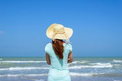 Girl looking at the sea. Dressed girl with hat looking at the sea Stock Photo