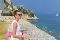 Girl looking at the sea from the fortress wall. Girl looking at the sea from the new fortress in kerkyra wearing pink dress and sunglasses Stock Photo