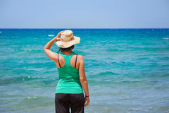 Girl looking at the sea. Girl with a hat looking at the sea, Sardinia. Italy Royalty Free Stock Photography