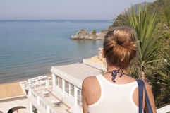 Girl looking on the sea horizon. Girl is looking to the distance from the balcony of calm hotel of Corfu island, Greece Stock Image
