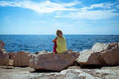 Girl looking into sea. Little girl sitting in the rock observing blue sea Stock Photos