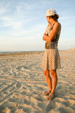 Girl looking at the sea on the seashore. Full-length portrait of a woman looking away the camera on the beach royalty free stock photos