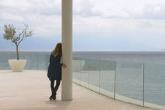 Girl looking at the sea and sky horizon from the terrace. Beautiful girl is standing on the white marble terrace (balcony) and looking the blue sea and sky and Stock Images