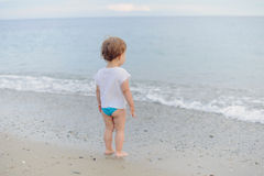 Girl Looking at Sea. Girl standing on sand and looking at sea Stock Photography
