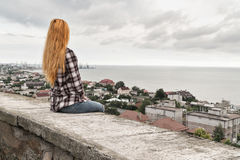 Girl looking at the sea. Woman sits on the parapet with her back to the camera and looks at the sea and the cloudy sky Royalty Free Stock Photography