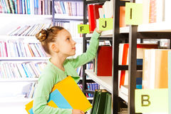 Girl looking and searching books in library Stock Photo