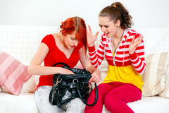 Girl looking on searching something girlfriend. Indignant young girl sitting on sofa and looking on searching something in handbag girlfriend Royalty Free Stock Photography