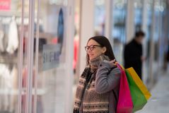 Girl looking at shop window. Happy shopaholic girl with shopping bags standing in front of store window and looking clothes stock photo