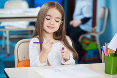 Girl Looking At Sketch Pen In Classroom Royalty Free Stock Photos