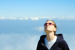 Girl looking in the sky. Smiling girl looking in the blue cloudy sky with copyspace Royalty Free Stock Photography