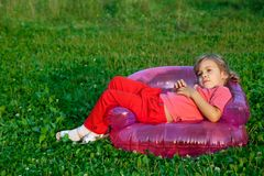Girl looking at the sky in inflatable armchair Royalty Free Stock Photos