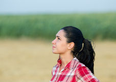 Girl looking at sky. Pretty young woman farmer standing in field and looking up at sky and waiting for rain Stock Photography