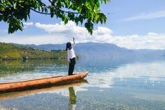 Girl looking into sky standing on canoe Stock Image