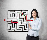 Girl is looking for the solution of the maze. Concrete background. Royalty Free Stock Image