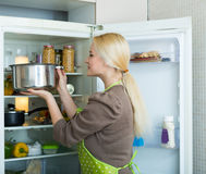 Girl looking for something in fridge. Blonde girl looking for something in fridge at home kitchen Royalty Free Stock Image