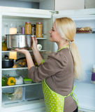 Girl looking for something in fridge. Blonde russian girl looking for something in fridge at home kitchen Stock Photo