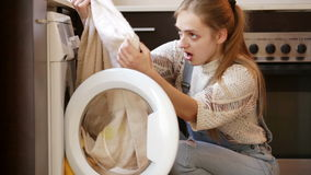 Girl looking at stains on towels. Upset girl looking at stains on towels after laundry stock video footage