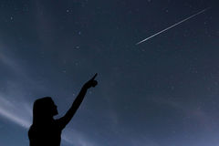 Girl looking at the stars. Girl making a wish by seeing a shooti Stock Images