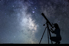Girl looking at the stars with telescope. Milky Way galaxy. Royalty Free Stock Photography