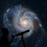 Girl looking at the stars with telescope. Pinwheel Galaxy royalty free stock photo