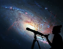 Girl looking at the stars with telescope. Spiral Galaxy M106 Stock Photography