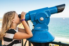 Girl looking through a stationary paid telescope. Blond Caucasian school girl is looking through a stationary paid telescope stands on sea coast Stock Photography
