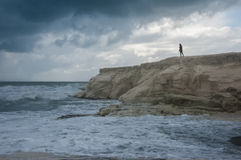 A girl looking at the stormy sea Stock Images