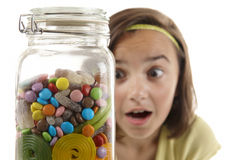 Girl looking at sweet jar Royalty Free Stock Images