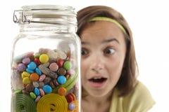 Girl looking at sweet jar Royalty Free Stock Images